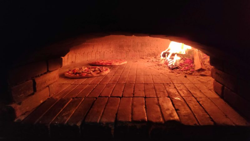 窯の中でピザが焼かれる様子
